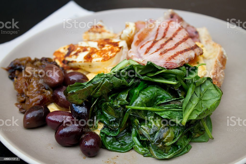 Scrambled eggs, spinach, haloumi, ham, olives and onions royalty-free stock photo