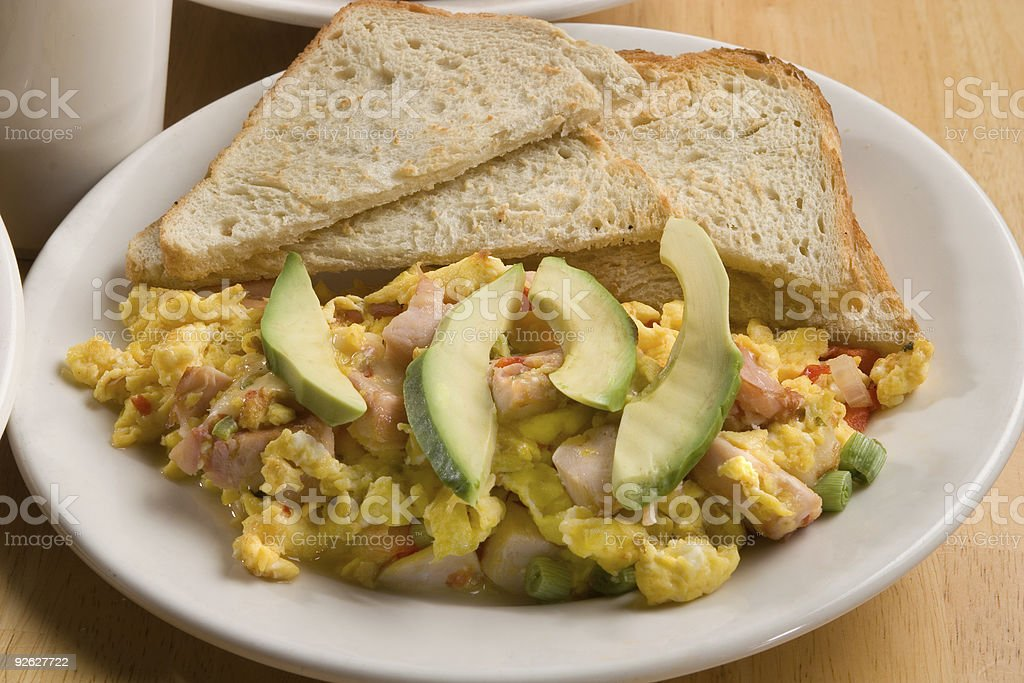 scrambled eggs, toast with avocado slices and ham stock photo