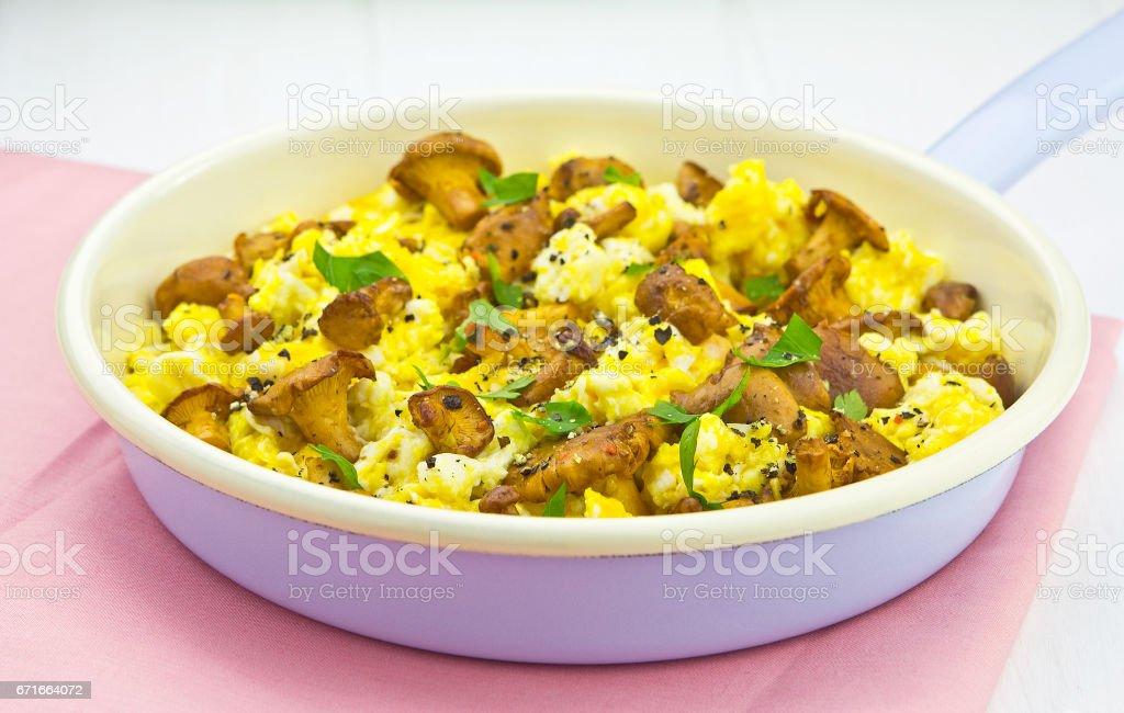 Scrambled eggs with chanterelle mushrooms stock photo