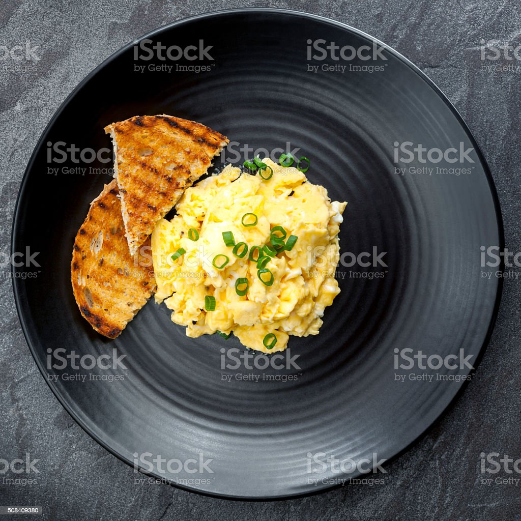 Scrambled Eggs with Toast on Black Plate stock photo
