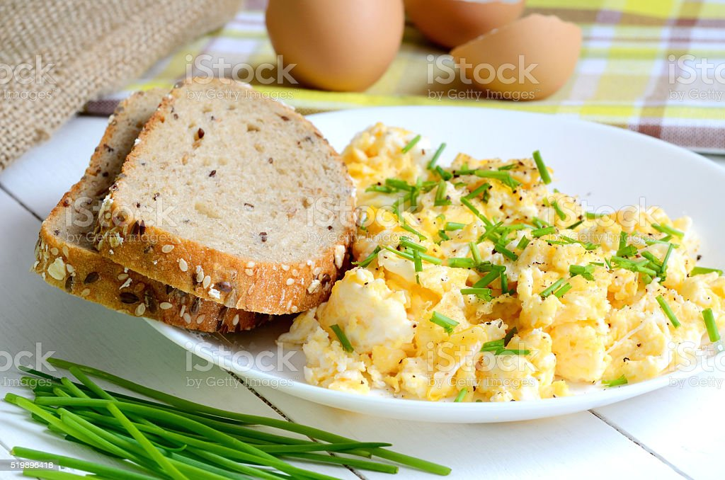 Scrambled eggs with wholemeal bread and fresh chives stock photo