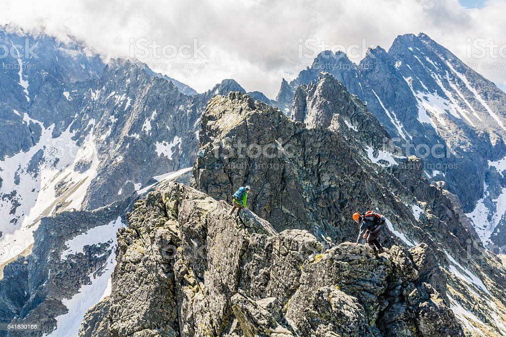 Scrambling for a difficult ridge. stock photo
