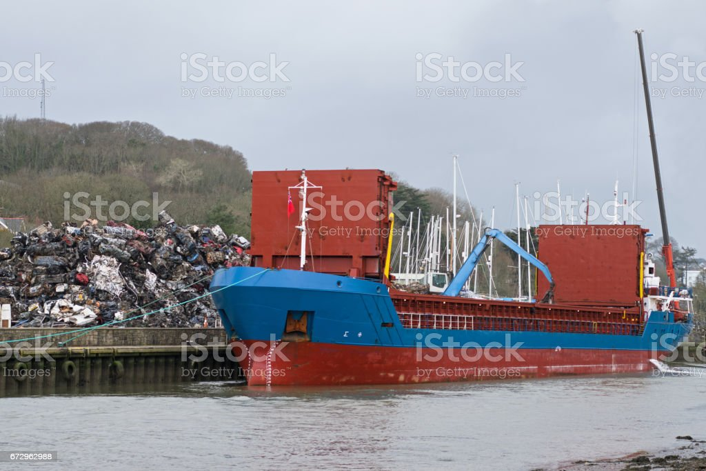 Scrap metal cargo being loaded aboard ship stock photo