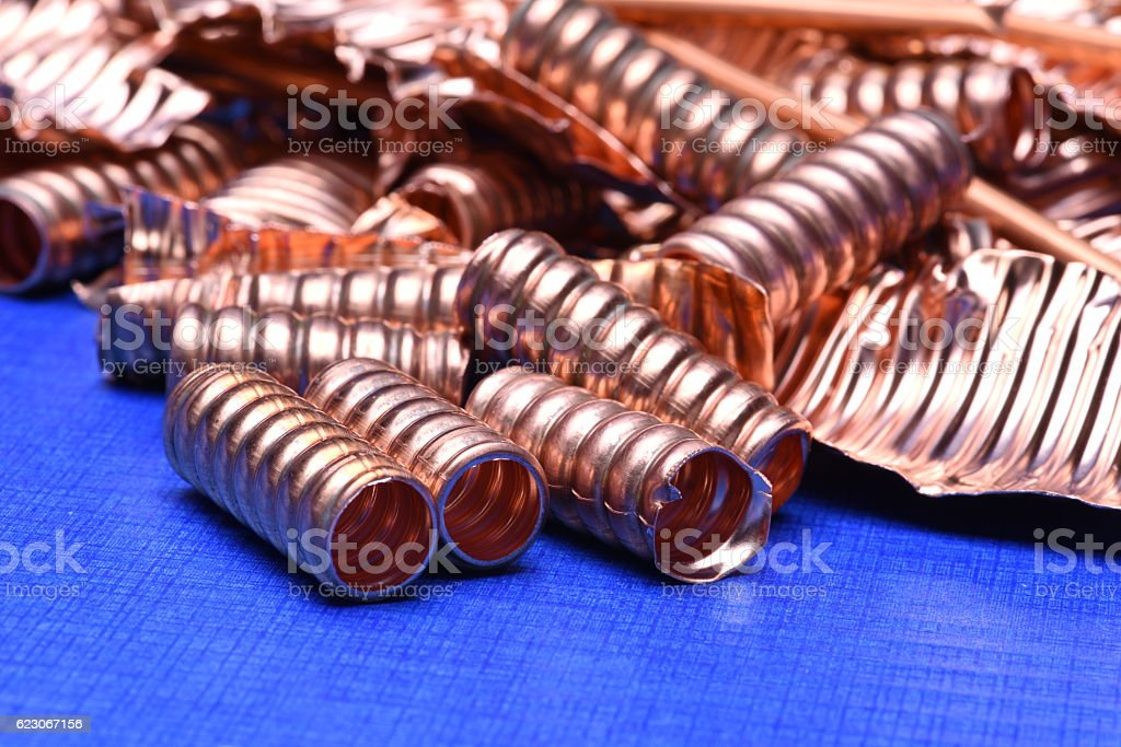 Scrap of copper for recycling on blue background stock photo