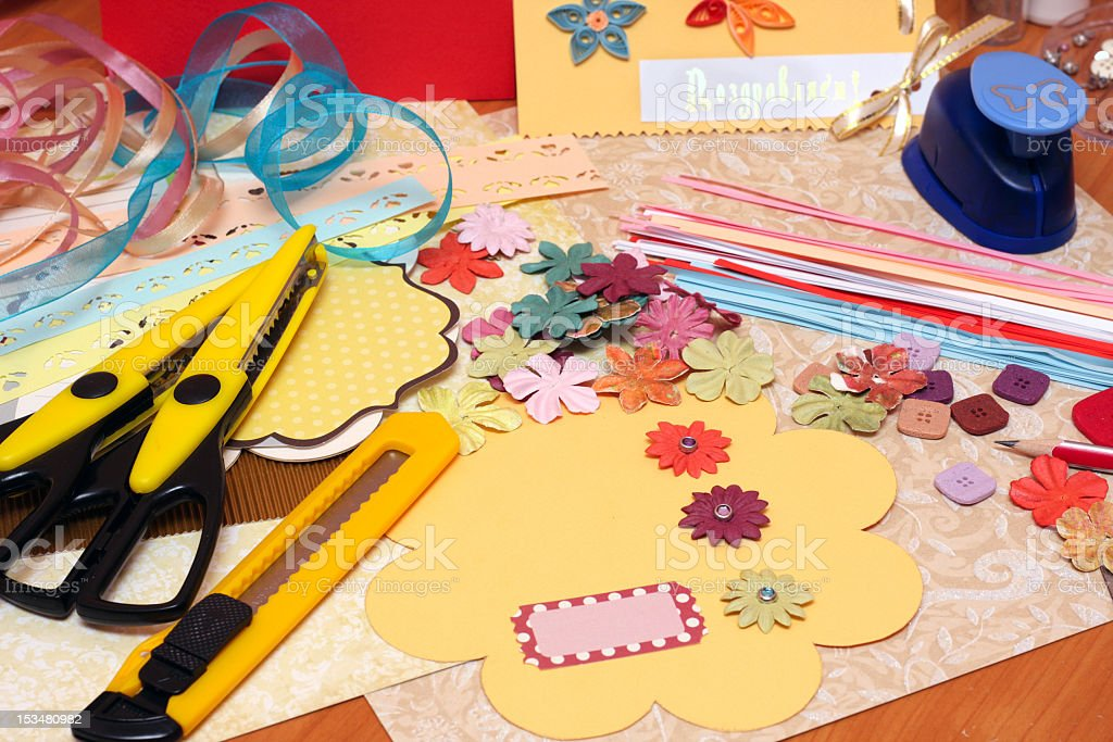 Scrapbooking supplies and tools scattered on table stock photo