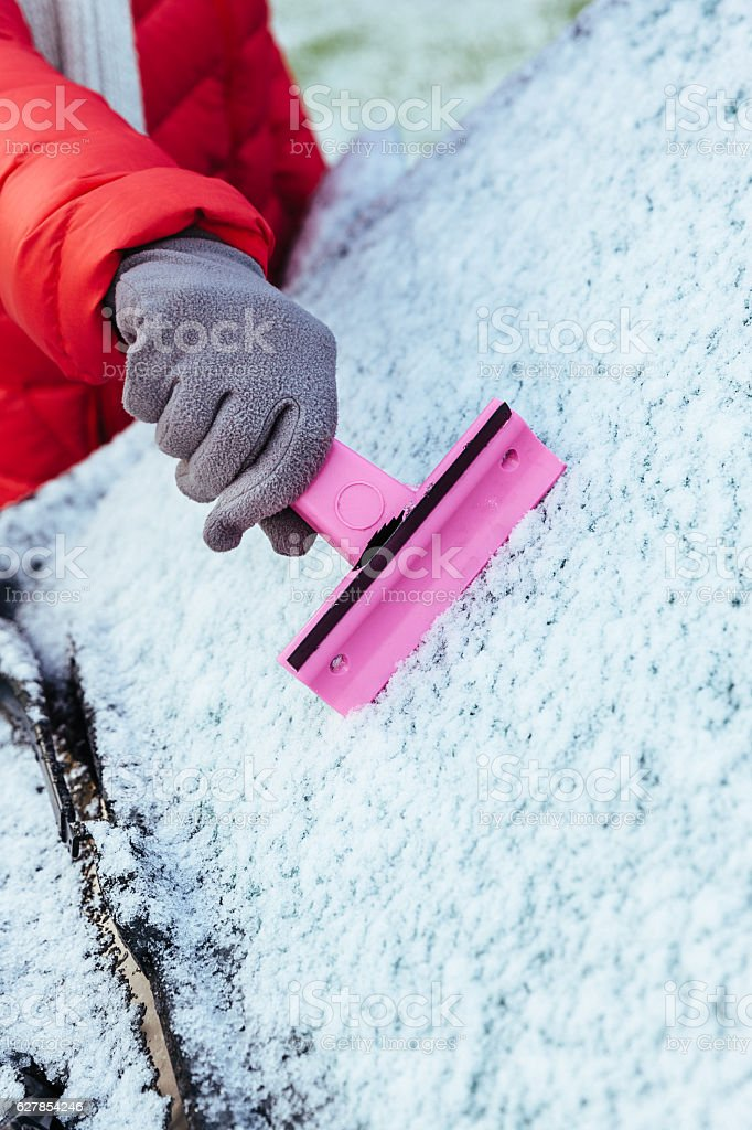 Scraper clearing frost from car windshield stock photo