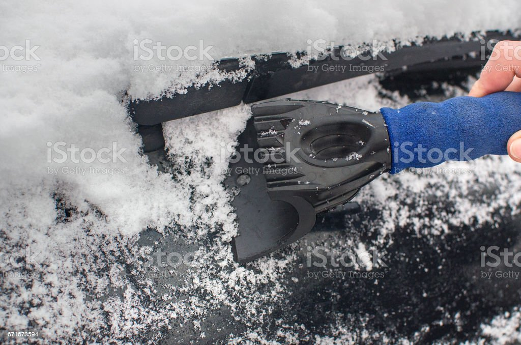 Scraping ice and snow from the car window stock photo