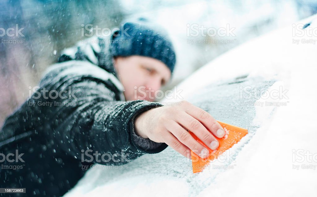 Scraping ice and snow from the windshield stock photo