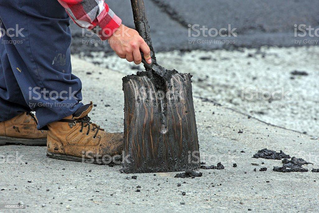 Scraping Sticky Asphalt From A shovel stock photo