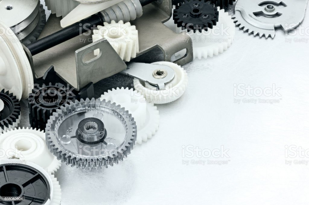 scratched metal industrial background with plastic cogwheels and machine parts stock photo