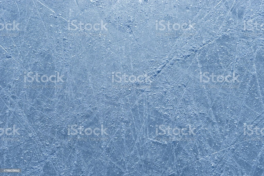 Scratched surface of ice rink strewn with the shards stock photo