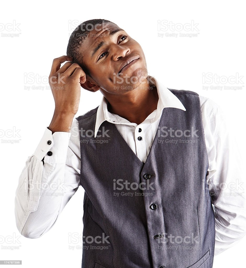 Scratching his head, a smiling young man thinks things over royalty-free stock photo