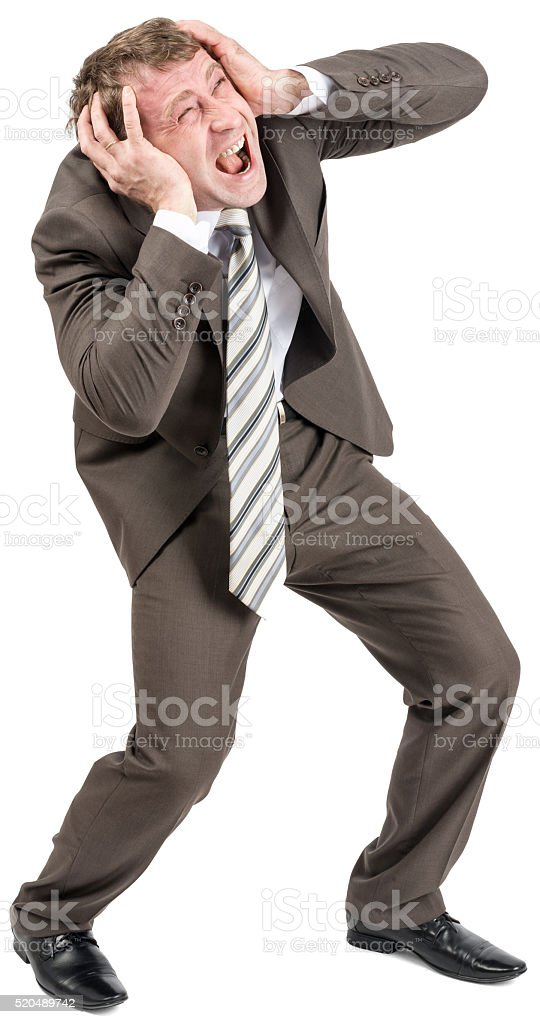 Screaming businessman covering his ears stock photo