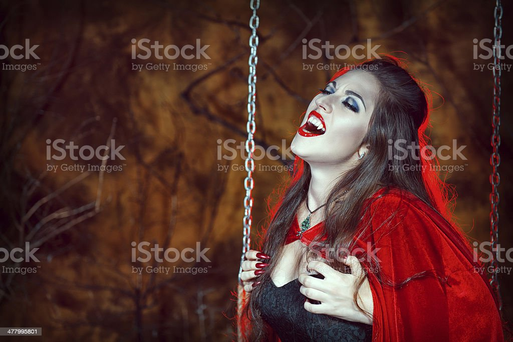Screaming halloween woman in red cloak on the swing royalty-free stock photo