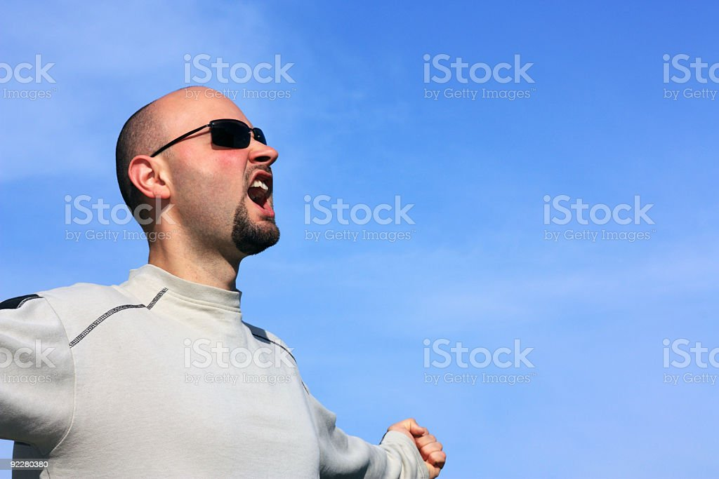 Screaming young man with sun glasses against blue sky royalty-free stock photo