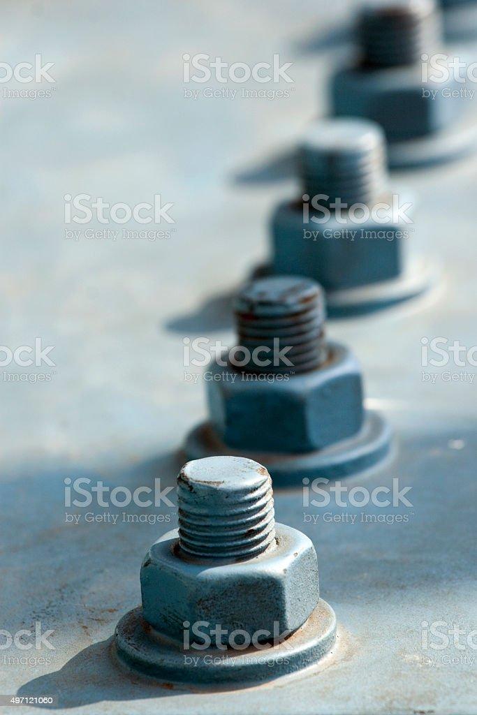 Screw and bolts on a massive girder gray bridge. Original stock photo