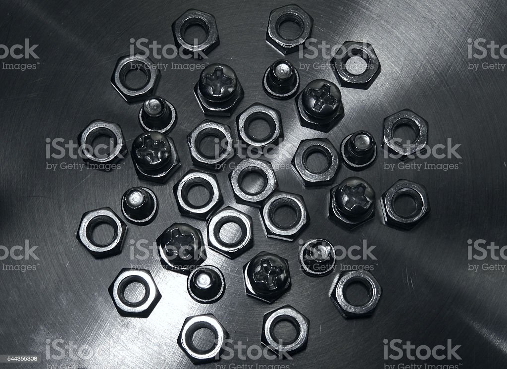 Screw bolts and hex nuts on metal surface closeup stock photo