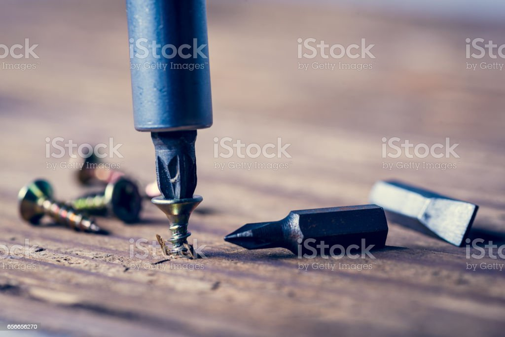 screw with a screwdriver stock photo