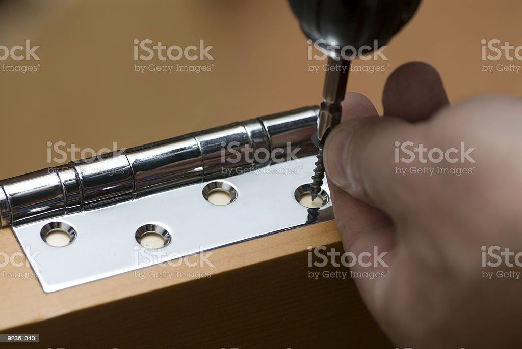 Screwdriver screwing a nail into the hinge of a door stock photo