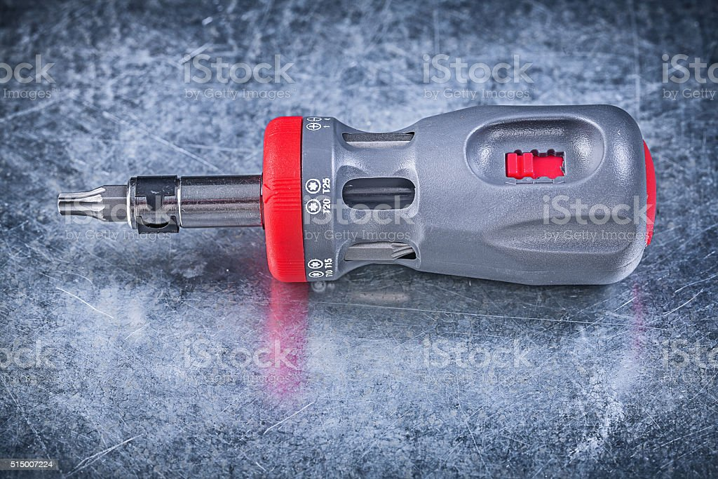 Screwdriver with replaceable bits on metallic background constru stock photo