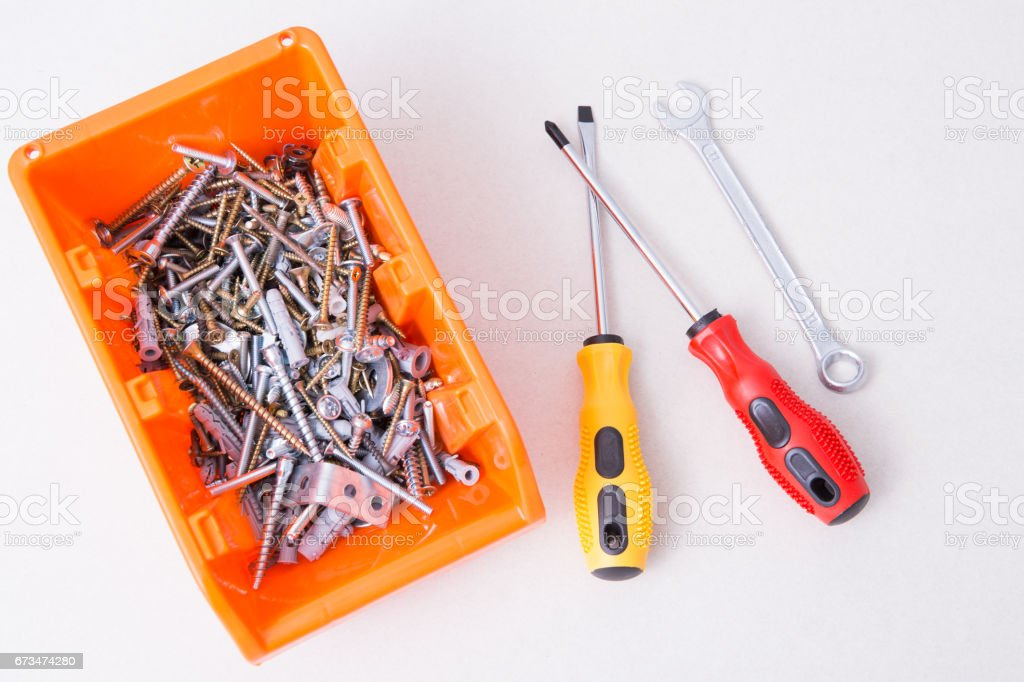 Screwdrivers and wrench near the plastic container with screws, bolts, dowels and confirmats stock photo