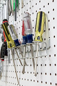 Screwdrivers hanging on a white pegboard