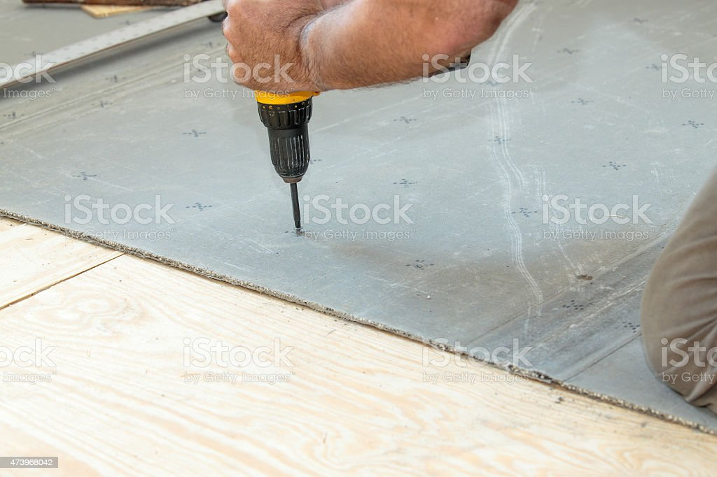 Screwing cement board to the subfloor stock photo