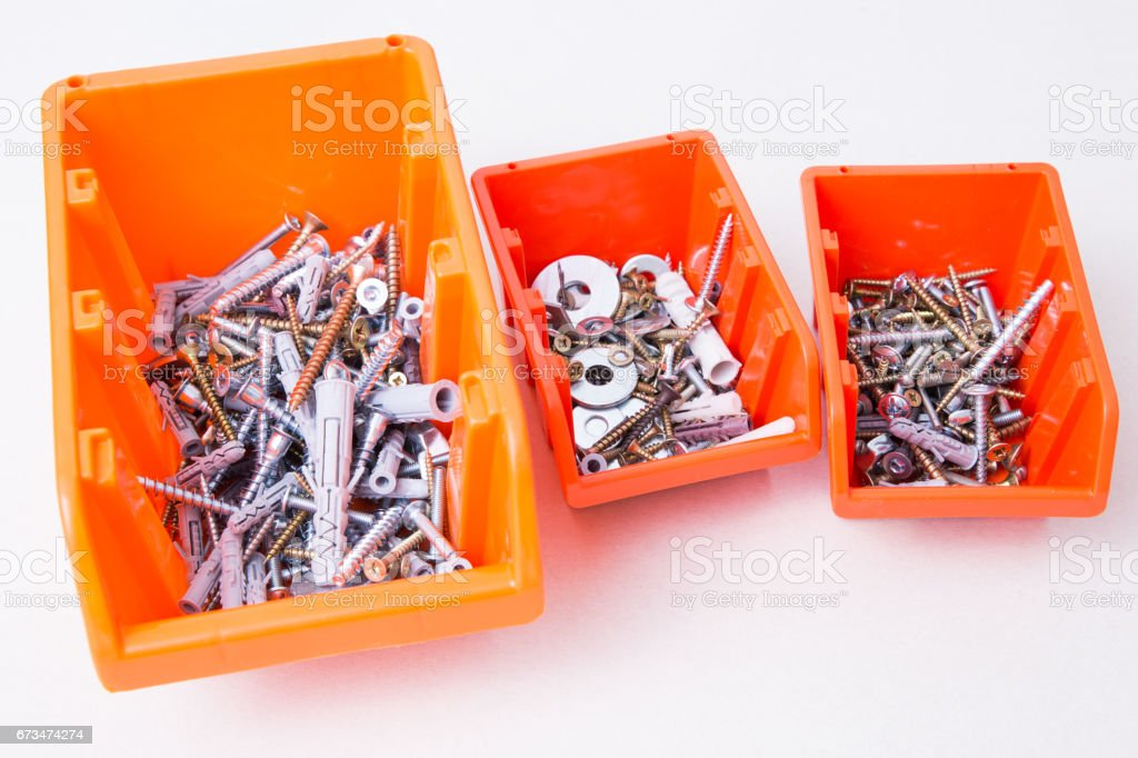 Screws and bolts in orange containers different size. stock photo