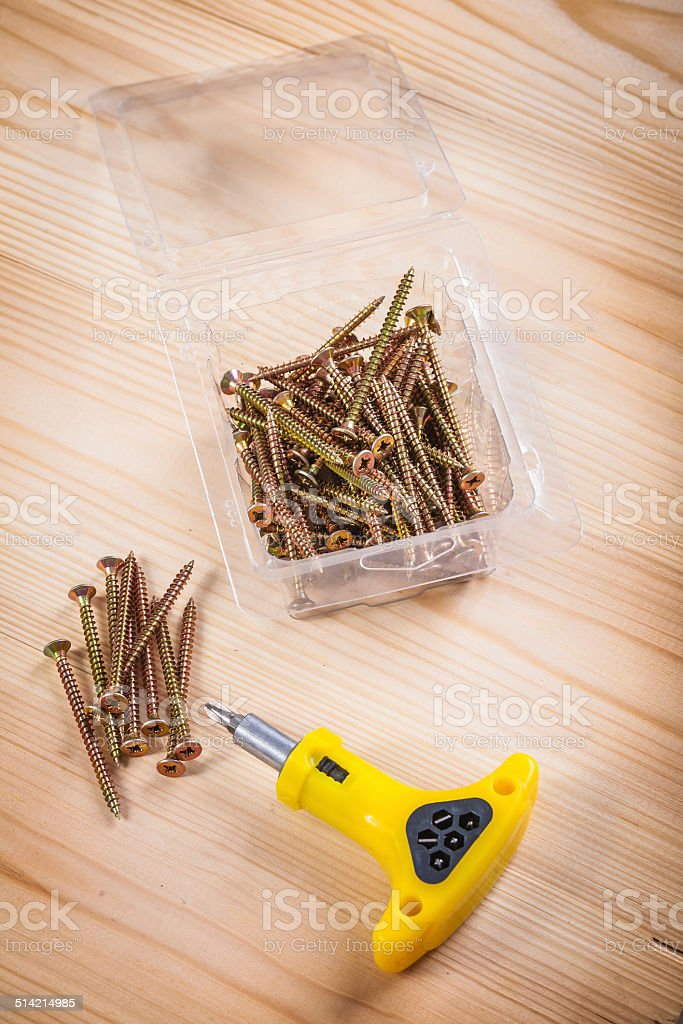 screws and screwdriver on wooden board stock photo