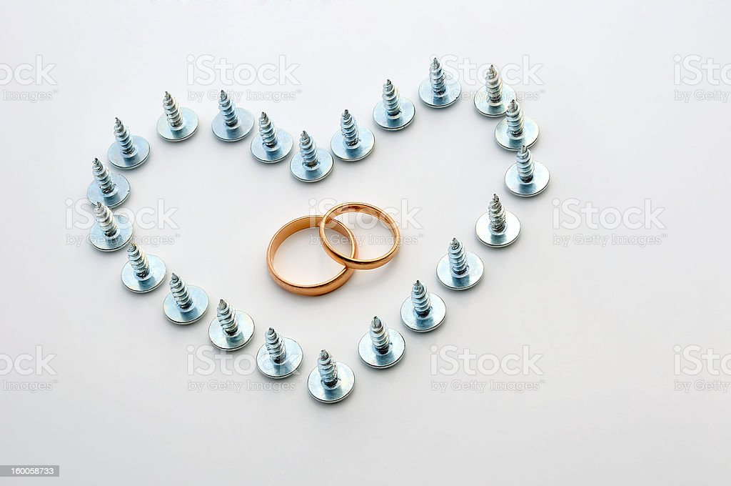 Screws and wedding rings stock photo