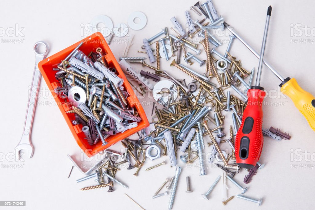 Screws, bolts, dowels in orange container and screwdriver with magnetic tips. stock photo