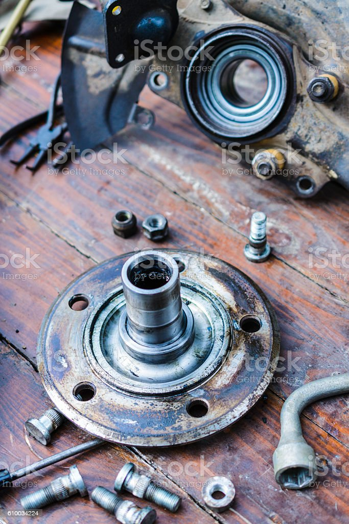 Screws for mounting the wheel hub lie on a wooden stock photo