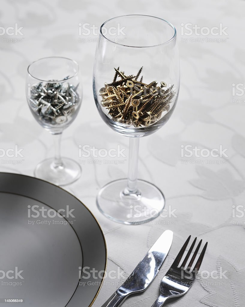 Screws in wine glasses at table stock photo