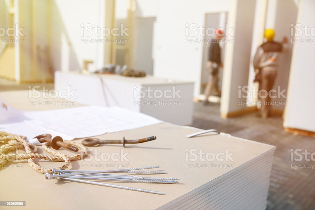 Screws on plasterboard panels with workers stock photo