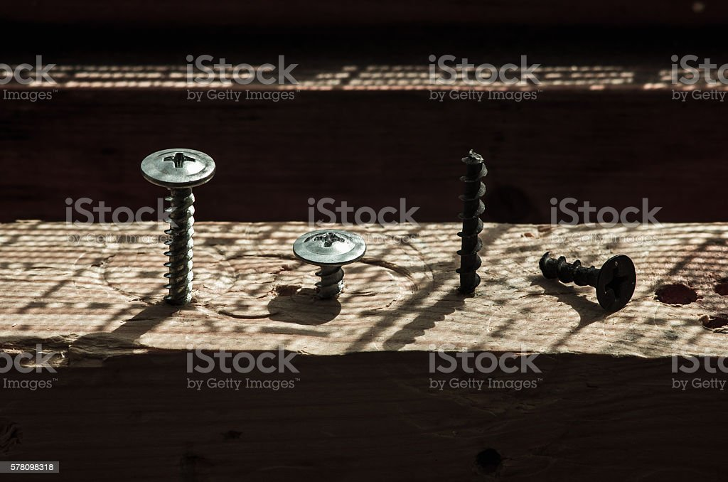 Screws screwed in the board game of light and shadow stock photo