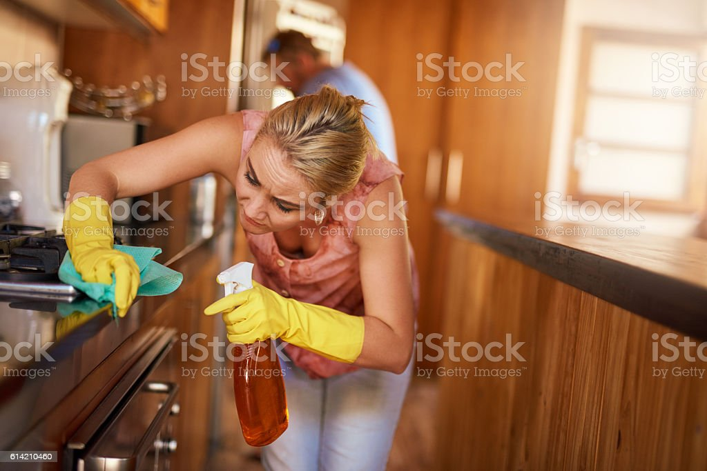Scrubbing her way to a spotless kitchen stock photo