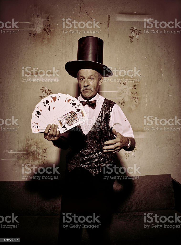 Scruffy old magician doing card trick royalty-free stock photo