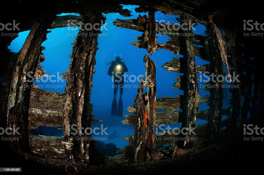 Scuba diver behind the wreck royalty-free stock photo