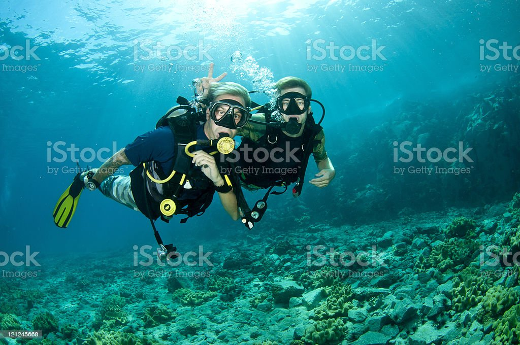 Scuba diver giving a peace sign over another diver's head  stock photo