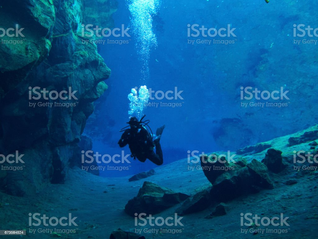 Scuba Diver in Scorpion Position Near Sandy Rocky Bottom in Clear Water Continental Split at Silfra in Deep Section at Pingvellir National Park stock photo