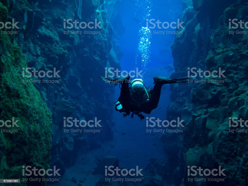Scuba Diver Off Center with Bubbles in Continental Split at Silfra in Deep Section at Pingvellir National Park stock photo