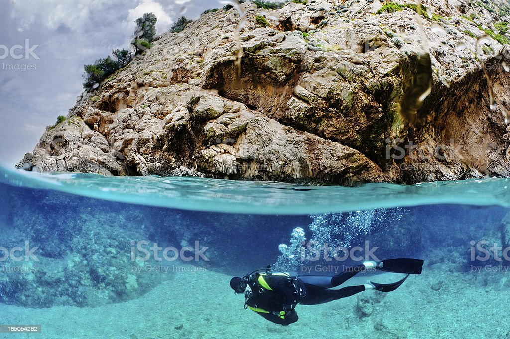 Scuba diver under the rock stock photo