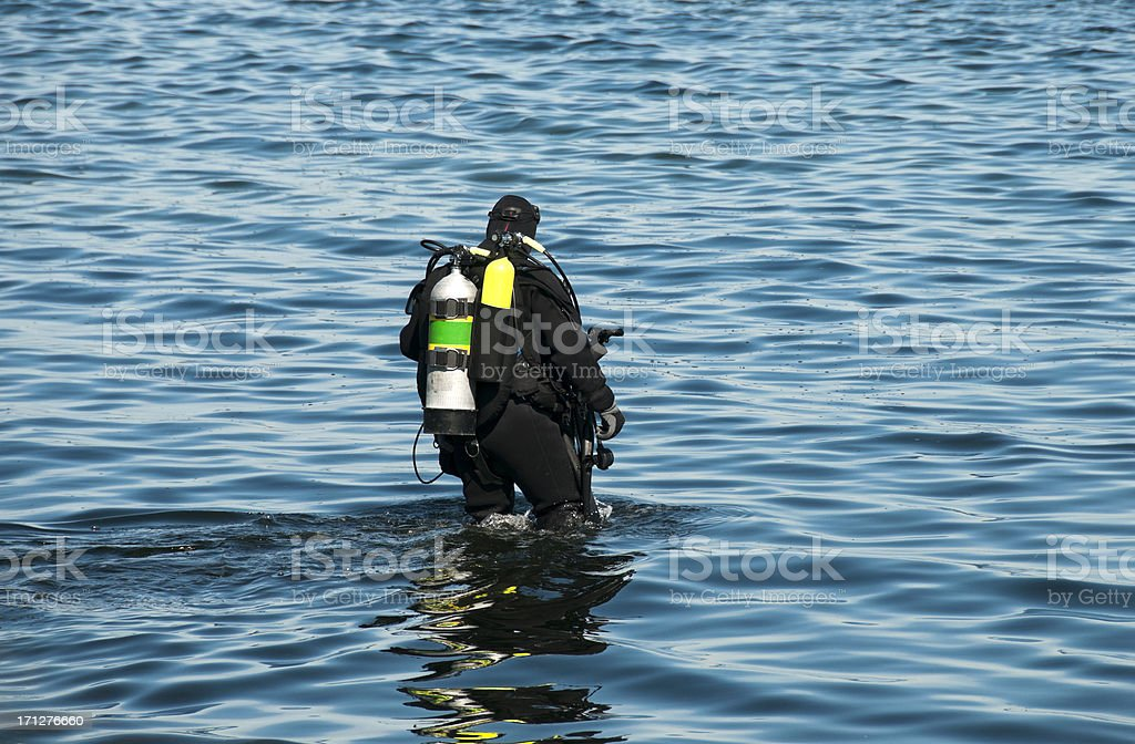 Scuba diver wading into Puget Sound with underwater camera royalty-free stock photo
