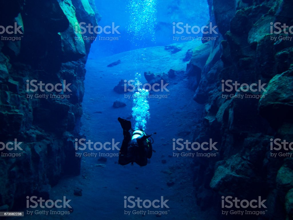Scuba Diver with Bubbles Mid Kick in Continental Split at Silfra in Deep Section at Pingvellir National Park stock photo