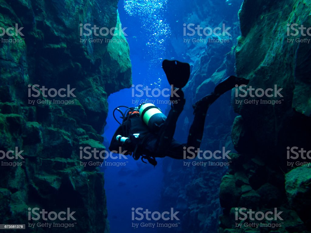 Scuba Diver with Buoyant Floating Feet Without Bubbles Inside Continental Split at Silfra in Deep Section at Pingvellir National Park stock photo