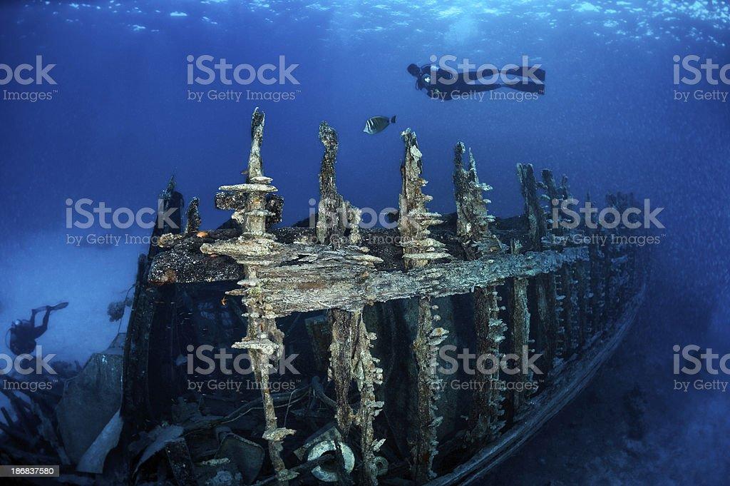 Scuba Divers Exploring The Sunken Ship royalty-free stock photo