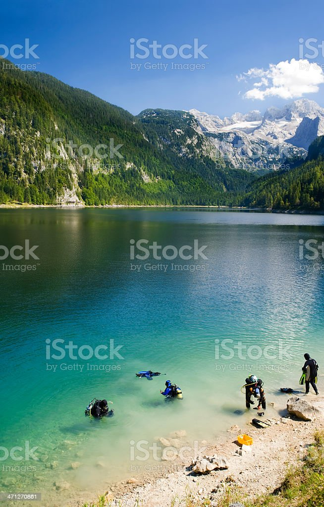 Scuba divers in an alpine lake with Mountains and Glaciers royalty-free stock photo
