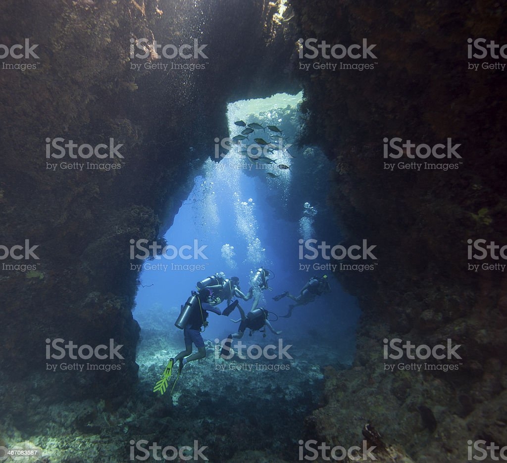 Scuba divers in an underwater cavern royalty-free stock photo