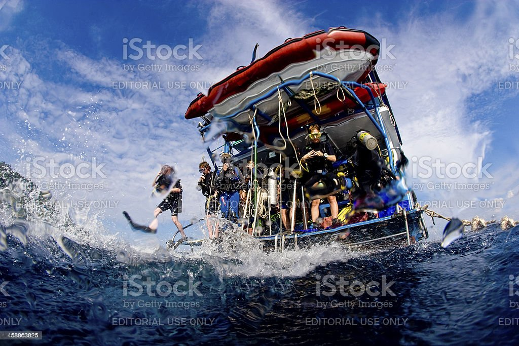 Scuba divers jumping in the ocean from dive boat stock photo