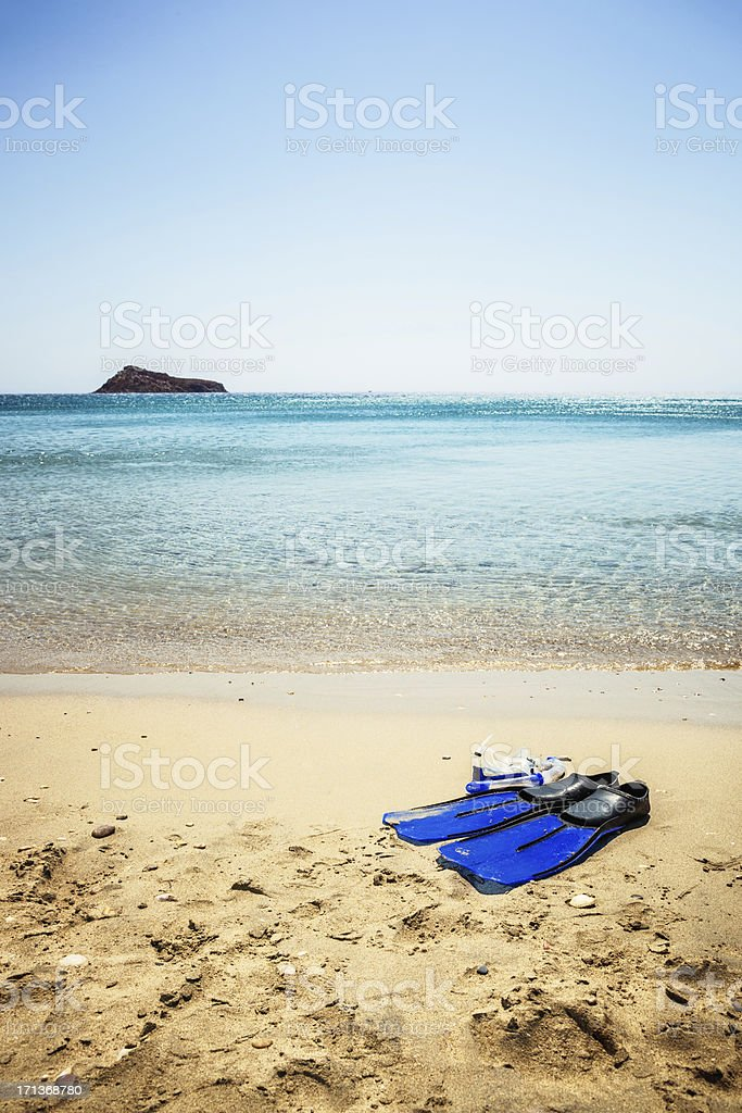 Scuba diving mask and fins on sandy beach royalty-free stock photo